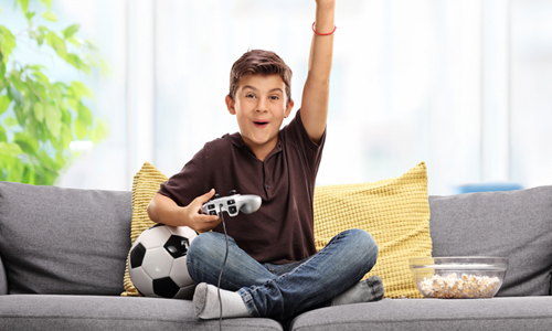 Young boy seated on couch with video game controller